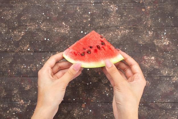 Bovenaanzicht vrouwelijke bedrijf watermeloen stuk op bruin