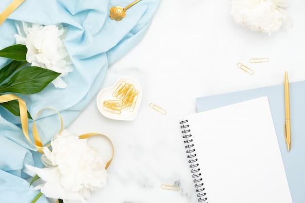 Bovenaanzicht vrouwelijke gouden accessoires, papieren notitieblok, pioenrozen