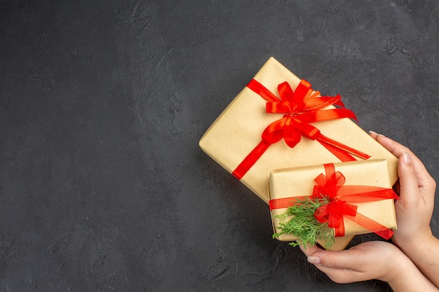 Bovenaanzicht vrouwelijke hand met grote en kleine kerstcadeaus in bruin papier vastgebonden met rood lint dennentak op donkere ondergrond