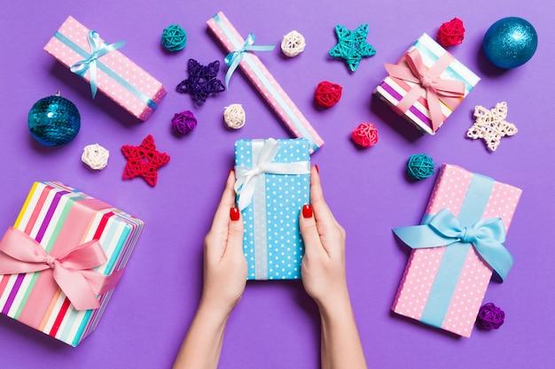 Bovenaanzicht vrouwelijke handen met een kerstcadeau op feestelijke paars. vakantiedecoratie, speelgoed en ballen. vakantie