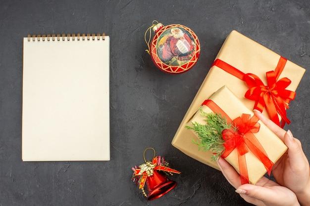Bovenaanzicht vrouwelijke handen met kerstcadeau in bruin papier gebonden met rood lint kerstboom speelgoed notitieblok op donkere achtergrond