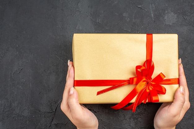 Bovenaanzicht vrouwelijke handen met kerstcadeau in bruin papier vastgebonden met rood lint op donkere ondergrond