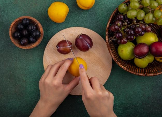 Bovenaanzicht vrouwelijke handen snijden nectacot met mes en plukken op snijplank met druiven en plukken in mand en druiven bessen in kom met nectacots op groene achtergrond