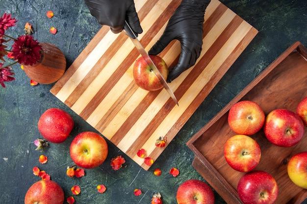Bovenaanzicht vrouwelijke kok die appels snijdt op het grijze oppervlak