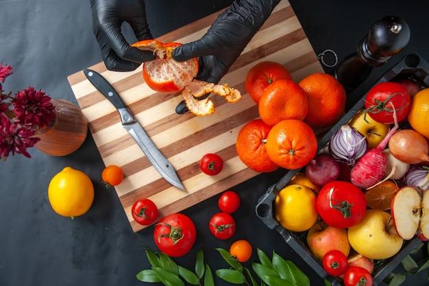 Bovenaanzicht vrouwelijke kok die mandarijnen op het donkere oppervlak schoonmaakt