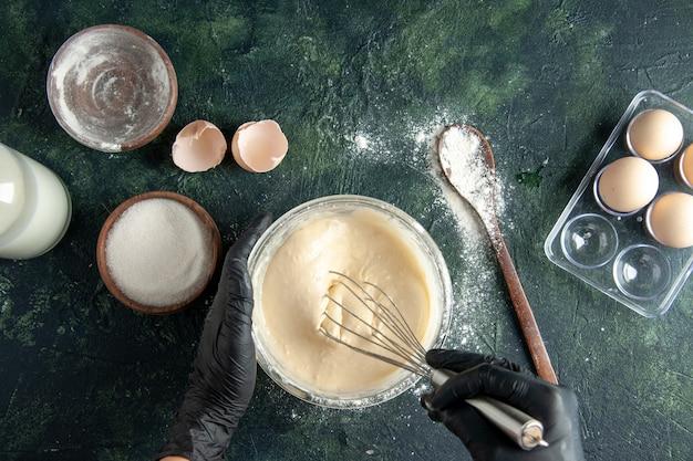 Bovenaanzicht vrouwelijke kok ingrediënten mengen en deeg maken op donkere ondergrond