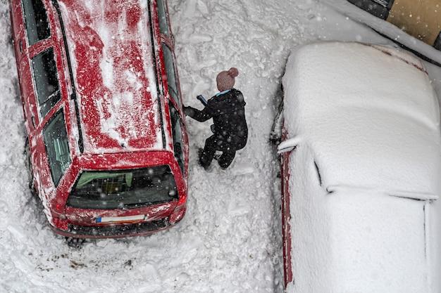Bovenaanzicht vrouwelijke schoonmaak rode auto vallende sneeuw voor het rijden na zware sneeuwstorm sneeuwval