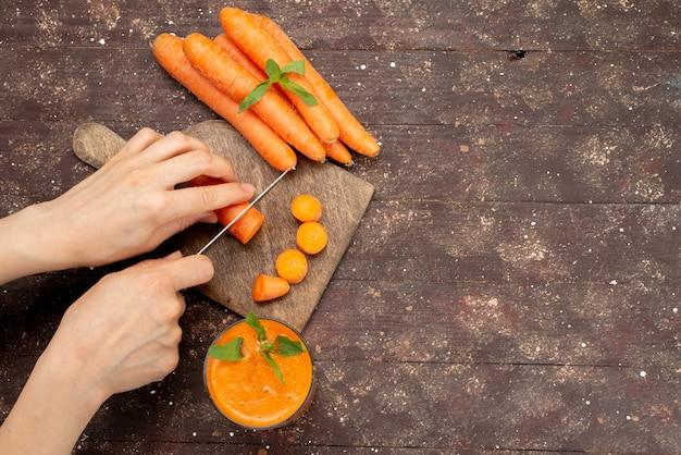 Bovenaanzicht vrouwelijke snijwortel op bruin houten bureau samen met vers wortelsap op bruin