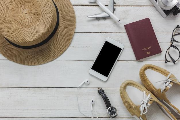 Bovenaanzicht vrouwen accessoires om te reizen concept.white mobiele telefoon, vliegtuig, hoed, paspoort, horloge, bril op houten tafel.
