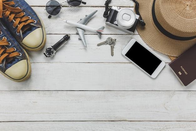 Bovenaanzicht vrouwen accessoires om te reizen concept.white mobiele telefoon, vliegtuig, hoed, paspoort, horloge, zonnebril op houten tafel.