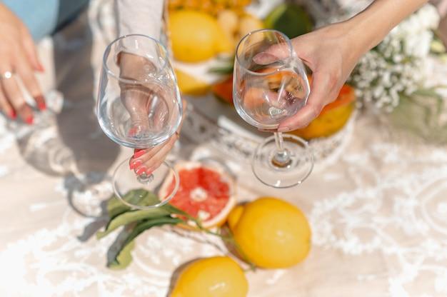 Bovenaanzicht vrouwen handen met twee lege glazen om te vullen met sap van wijn. verscheidenheid aan fruit op de achtergrond. vrouwtjes zittend op deken tijdens picknick.