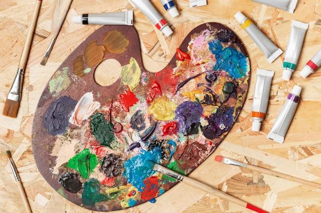 Bovenaanzicht vuile kleurenpalet en aquarelbuizen