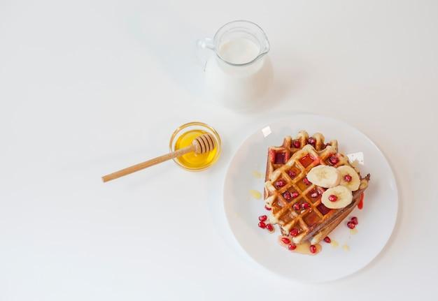 Bovenaanzicht wafel met honing en melk