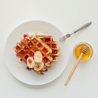 Bovenaanzicht wafel met honing en vork