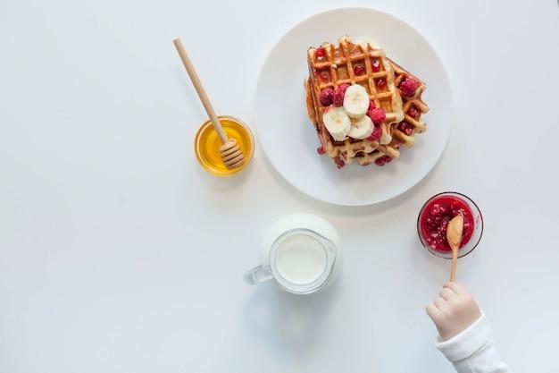 Bovenaanzicht wafel met jam, melk en honing