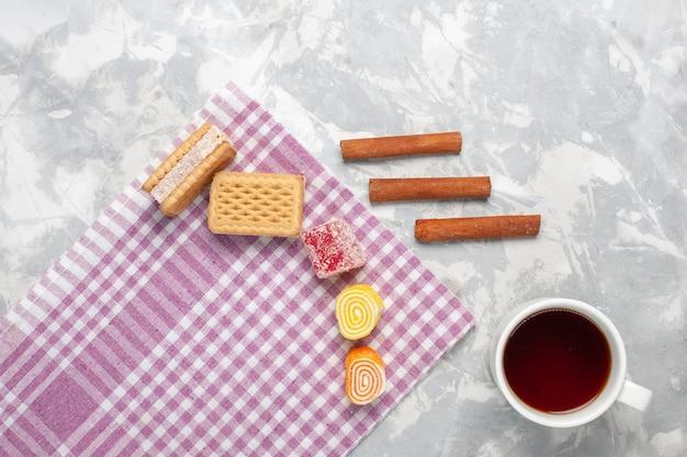 Bovenaanzicht wafels en kaneel met kopje thee op witte achtergrond