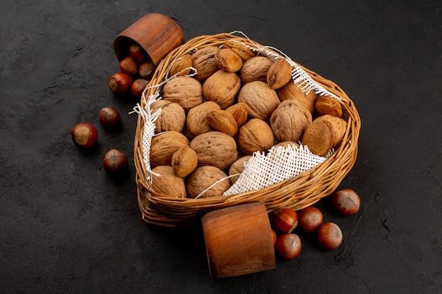 Bovenaanzicht walnoten en hazelnoten in mand en bruine pot op de donkere achtergrond