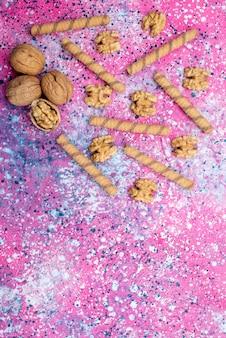Bovenaanzicht walnoten en koekjes verspreid over de gekleurde achtergrond crackers kleuren knapperige noot