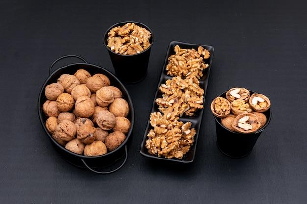 Bovenaanzicht walnoten in zwart servies op zwart horizontaal