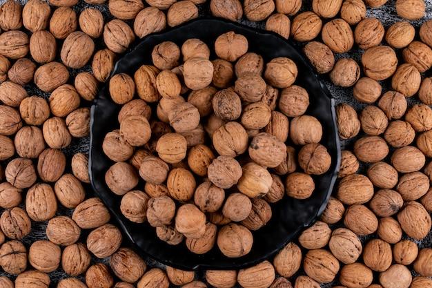 Bovenaanzicht walnoten in zwarte plaat omgeven door horizontale walnoten