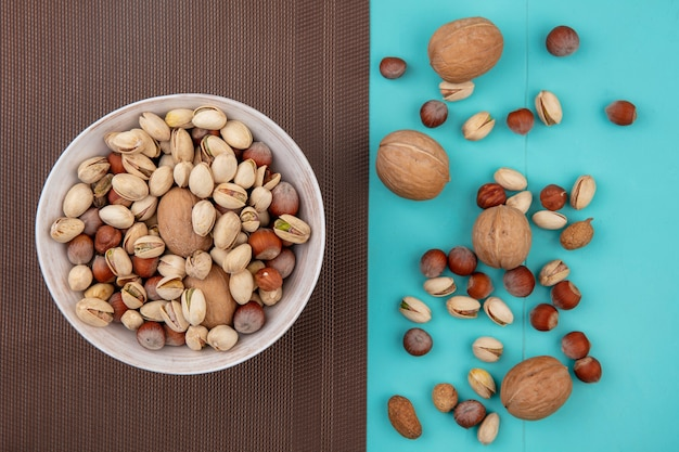 Bovenaanzicht walnoten met hazelnoten met pistachenoten in een kom op een bruine handdoek op een turquoise tafel