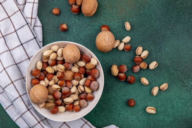 Bovenaanzicht walnoten met hazelnoten, pistachenoten en pinda's in een kom met een geruite handdoek op een groene tafel