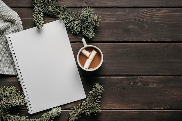 Bovenaanzicht warme chocolademelk met lege notebook en kopie-ruimte