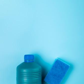 Bovenaanzicht wasmiddel en spons op blauwe achtergrond