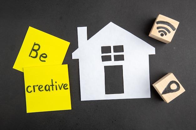 Bovenaanzicht wees creatief geschreven op plaknotitie wifi en locatiepictogrammen op houten kubussen papieren huis op zwart oppervlak