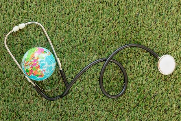 Bovenaanzicht wereldbol met stethoscoop op gras
