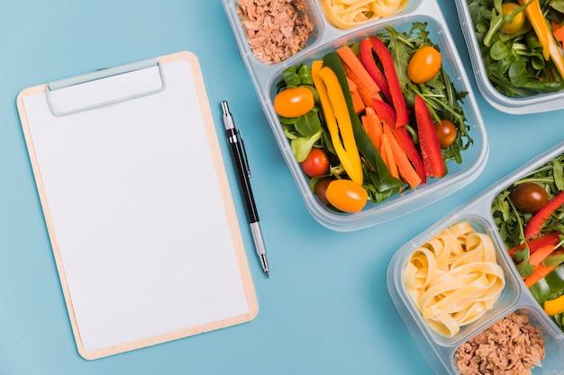Bovenaanzicht werk lunchboxen met lege notebook