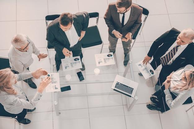 Bovenaanzicht werkgroep die financiële gegevens bespreekt