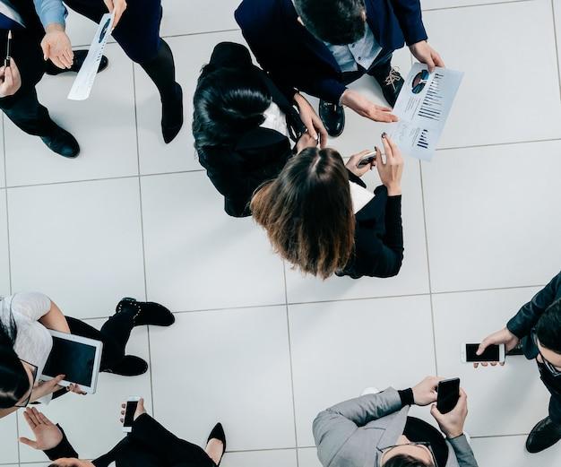 Bovenaanzicht. werknemers die vóór de vergadering financiële gegevens bespreken. bedrijfsconcept