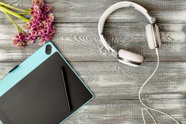 Bovenaanzicht werkplek met digitale tablet en grafische pen, hoofdtelefoons en bloem