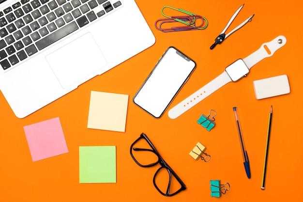 Bovenaanzicht werkruimte concept met oranje achtergrond