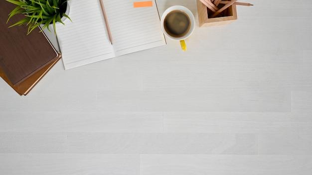 Bovenaanzicht werkruimte met boek, laptop, potlood en koffie op witte houten tafel.