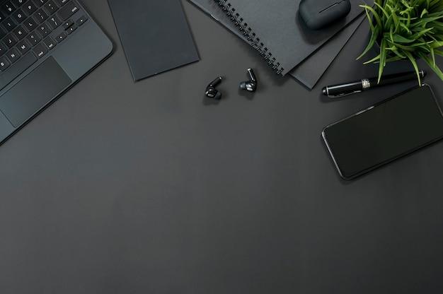 Bovenaanzicht werkruimte met smartphone, tablettoetsenbord en gadget op zwarte achtergrond, kopieer ruimte.