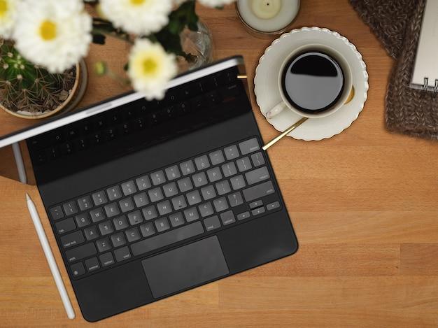 Bovenaanzicht werkruimte met tablet, toetsenbord, koffiekopje en bloem