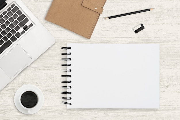Bovenaanzicht werkruimte voor zakelijke achtergrond. lege notitieboekje en bureaulevering op houten achtergrond.