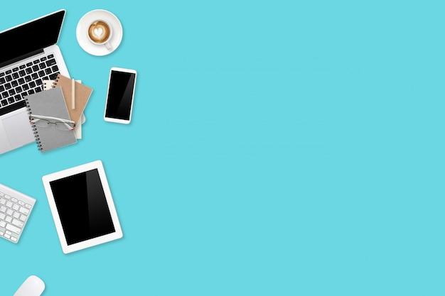 Bovenaanzicht werkruimte zakelijke groene en witte tafel met laptopcomputer, mobiele telefoon, tablet, kantoorbenodigdheden en koffiekopje gebruiken voor