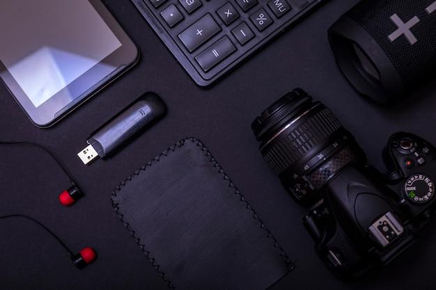 Bovenaanzicht werkruimtefotograaf met digitale camera, rekenmachine, usb-station en accessoire op zwarte tafel achtergrond met kopie ruimte.