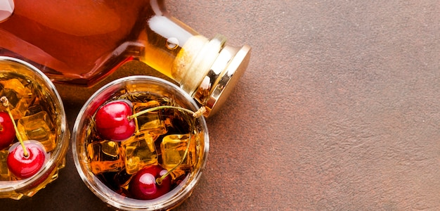 Bovenaanzicht whisky op de rotsen met kersen en fles met kopie-ruimte