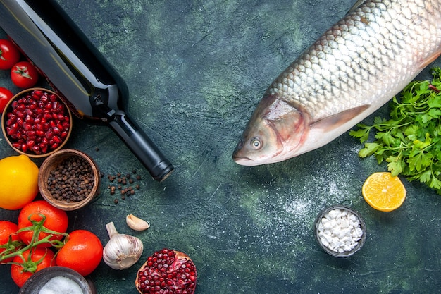 Bovenaanzicht wijnfles rauwe vis tomaten knoflook greens granaatappel verschillende kruiden in kleine kommen op tafel