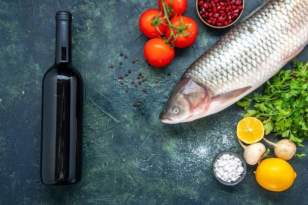 Bovenaanzicht wijnfles rauwe vis tomaten radijs peterselie granaatappel zeezout in kleine kommen citroen op tafel