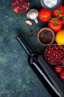Bovenaanzicht wijnfles tomaten knoflook granaatappel verschillende kruiden in kleine kommen op tafel