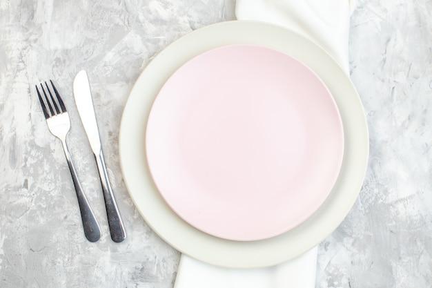 Bovenaanzicht wit bord met roze bord en bestek op lichte ondergrond keuken vrouwelijkheid horizontaal eten glas maaltijd kleur dames