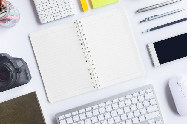 Bovenaanzicht wit bureaubureau. werkruimtetafel essentiële elementen op vlak leggen.
