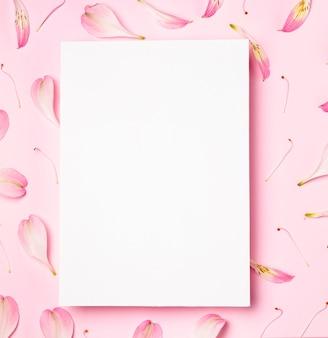 Bovenaanzicht wit frame omgeven door bloemblaadjes