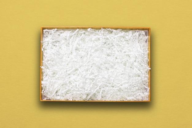 Bovenaanzicht, wit papiervuller in gele kartonnen doos
