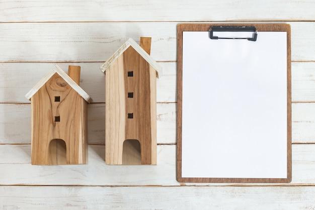 Bovenaanzicht, wit vel op klembord en naast heeft houten huis hout in investeringen in onroerend goed